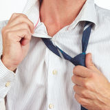 Guy unleashes his tie over bright shirt closeup Stock Image