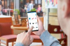 Guy use online store app for shopping clothes, electronic, motors. Coffee shop in background.  Stock Photography