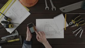 Top down view. A guy is checking information in the schematics stock footage