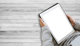 A guy using digital tablet, copy space on screen, on wooden floor Royalty Free Stock Photography