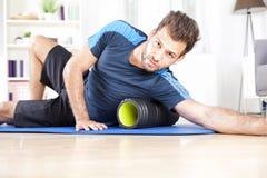 Guy Using Foam Roller atlético en ejercicio Imagen de archivo libre de regalías
