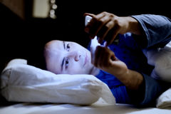 Guy using his mobile phone in the bed Royalty Free Stock Photo