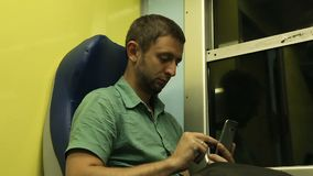 Guy using his mobile phone while traveling to another destination on night train. Stock footage stock video