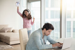 Guy using laptop computer, woman listening music on tablet indoo Royalty Free Stock Image