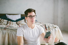 Guy using remote control while sitting on the bed in home. Happy attractive young man watching tv . Human emotions on Royalty Free Stock Photos