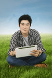 Guy using tablet on the meadow Royalty Free Stock Photography