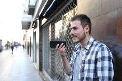 Guy using voice recognition on smart phone outside royalty free stock photography