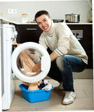 Guy using washing machine Royalty Free Stock Photo