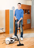 Guy  vacuuming with vacuum cleaner on parquet floor Stock Image