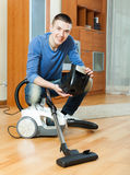 Guy vacuuming with vacuum cleaner on parquet floor in living roo Royalty Free Stock Photo