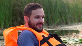 Guy in the vest on the river smile. Slow motion stock footage
