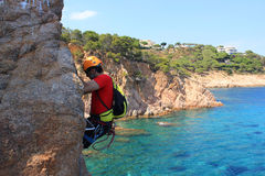 Guy in a via ferratas over the sea. In Gerona, Spain Royalty Free Stock Photography