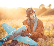 Guy in vintage clothes pilot with an airplane model outdoors Stock Photography