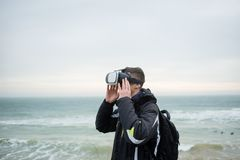 Guy in virtual reality glasses walks by the sea. A guy in virtual reality glasses walks by the sea and enjoys loneliness Stock Photo