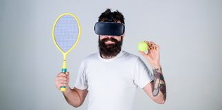 Guy with VR glasses play tennis with racket and ball. Man with beard in VR glasses play tennis, grey background. Hipster. On smiling face use modern technology Stock Photos