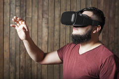 Guy with vr glasses showing gesture. Virtual reality glasses. Bearded man with virtual reality glasses standing over wooden background. concept of nosy royalty free stock photos
