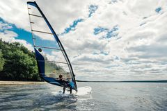 The guy in the waggon swims on the windsurf on lake. The guy in the waggon swims on the windsurf on the lake stock photo