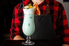 The guy waiter keeps alcoholic cocktail Blue Lagoon.  stock images