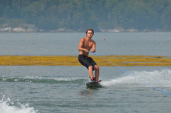 Guy Wakeboarding Behind a Boat in Maine`s Casco Bay. Young guy wakeboarding behind a boat in Casco Bay Maine Stock Images