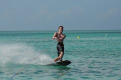 Guy Wakeboarding joven en las aguas azules tropicales de Aruba Fotos de archivo libres de regalías