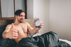 Guy is waking up. Man holding an alarm clock Bearded naked man showing thumbs up on the bed Royalty Free Stock Photo