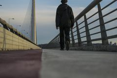 Guy walking on ada bridge in belgrade royalty free stock photo