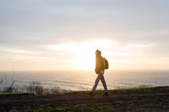 The guy is walking along the sea at dawn. A young slender guy with a backpack is walking along the sea along the precipice at dawn Royalty Free Stock Image