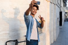 Guy walking with bicycle outdoors on the street take a selfie by mobile phone royalty free stock images