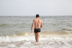 Guy walking into the sea Royalty Free Stock Photography