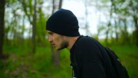 Guy Walking Through The Trees cansado en bosque almacen de video