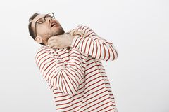 Guy wants kill himself not to listen boring stories anymore. Portrait of funny european man in glasses, holding hands on. Neck and bending backwards, choking Stock Images