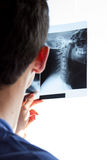 Guy watching neck radiogram. A doctor looking at a neck radiogram Royalty Free Stock Photo