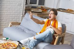 Man watching sport on tv at home alone unhappy. Guy watching sport on tv alone wearing scarf of his favorite team looking at screen disappointed unhappy losing Royalty Free Stock Photos