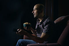 Guy watching TV with remote control at night Stock Images