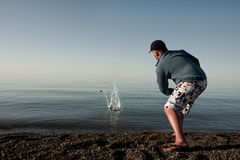 Guy at the water. The guy throws stones in water Stock Photos