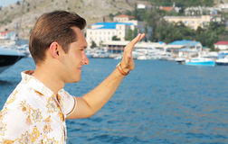 Guy waving his hand at sea, greeting hello Royalty Free Stock Photography