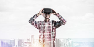 Guy wearing checked shirt and virtual mask demonstrating some em Royalty Free Stock Images