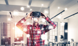 Guy wearing checked shirt and virtual mask demonstrating some em Royalty Free Stock Photo