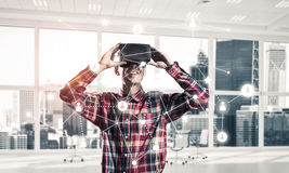 Guy wearing checked shirt and virtual mask demonstrating some em Royalty Free Stock Photos