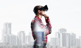 Guy wearing checked shirt and virtual mask with hand on chin. Young man with virtual reality headset or 3d glasses over cityscape background Stock Image