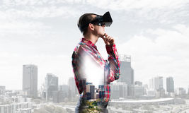 Guy wearing checked shirt and virtual mask with hand on chin Royalty Free Stock Image