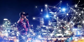 Guy wearing checked shirt and virtual mask holding his hand on chin. Young man with virtual reality headset or 3d glasses among connection lines Royalty Free Stock Photos