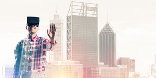 Guy wearing checked shirt and virtual mask stretching hand to to Stock Image