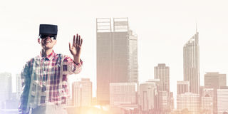 Guy wearing checked shirt and virtual mask stretching hand to to Stock Images