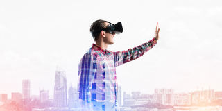 Guy wearing checked shirt and virtual mask stretching hand to touch something Stock Images
