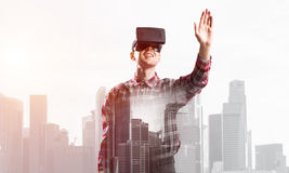 Guy wearing checked shirt and virtual mask stretching hand to touch something Royalty Free Stock Photo
