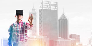 Guy wearing checked shirt and virtual mask stretching hand to touch something Stock Photography