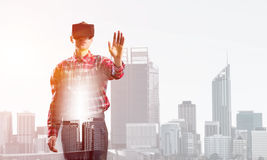 Guy wearing checked shirt and virtual mask stretching hand to touch something Stock Photo