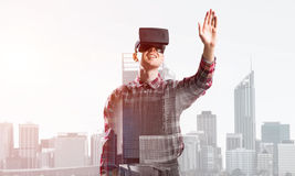 Guy wearing checked shirt and virtual mask stretching hand to touch something Stock Image