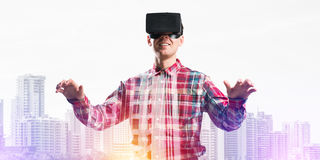 Guy wearing checked shirt and virtual mask stretching hands and trying to concentrate Royalty Free Stock Photo